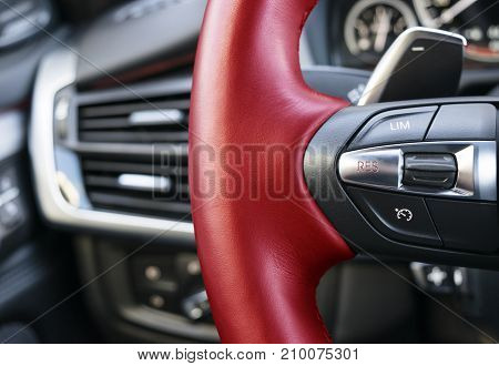 Cruise control buttons on the red steering wheel of a modern car car interior details