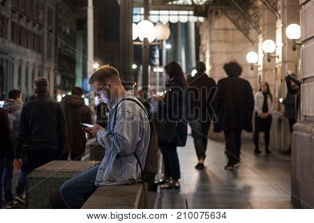 BELGRADE SERBIA - OCTOBER 14 201: Young white man using his smartphone at night in Belgrade a woman doing the same in the background. Serbia is one of the most phone equipped countries in Balkans