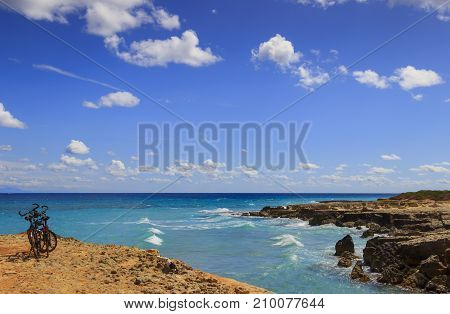 The most beautiful coast of Apulia: Torre Sant' Andrea, Otranto , ITALY (Lecce).Typical coastline of Salento: a pair of bikes for excursions. Seascape with cliffs, rocky arch and sea stacks.