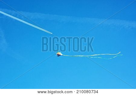 Flying colorful kite and airplane on the blue sky.