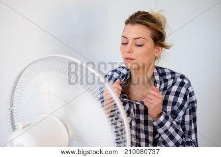 Girl face expression cooling in front of a fan