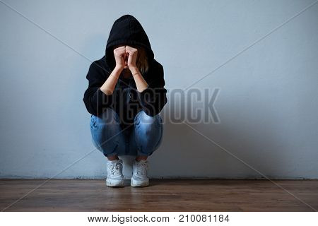 Young Girl Hiding Her Face Under Hooded Sweatshirt Isolated On Background
