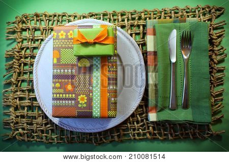 Birthday gifts in vintage mushroom and flowers paper on a white plate with plaid and green napkins and heavy woven mat horizontal aspect