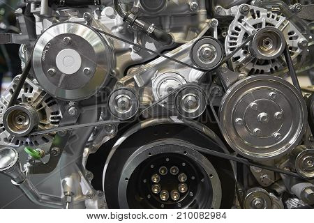 Close up view on new truck diesel engine motor belt, pulleys, gears, alternator and other engine equipment. Assembled truck diesel engine. Abstract auto automotive industrial background pattern