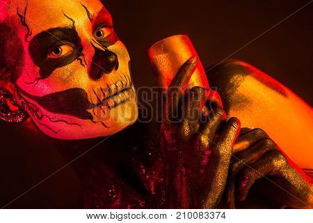 Pretty Girl With Skeleton Makeup Holds Glass