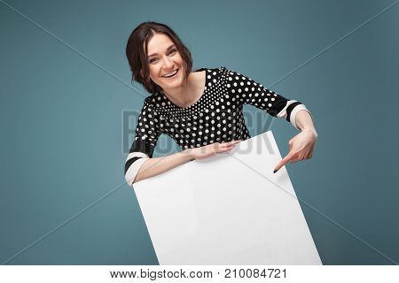 Picture Of Good Looking Woman In Speckled Clothes Standing With Big Paper In Hands
