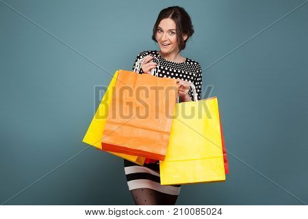 Image Of Beautiful Woman In Speckled Clothes Standing With Purchases In Hands