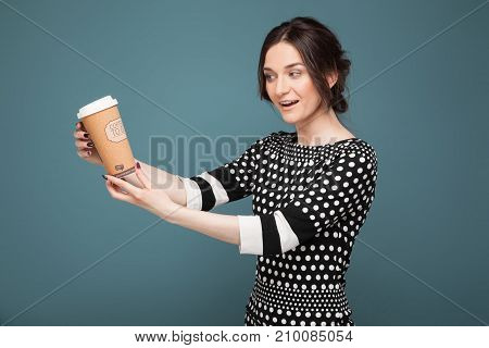 Picture Of Beautiful Woman In Speckled Clothes Standing With Coffe In Hands