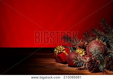 Fir tree branch with decoration, gift boxes lying on a wooden table on a red background.  New year and Christmas background with copy space for text. Greeting card.