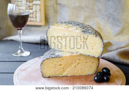 Homemade Maasdam Cheese On Wooden Board With Olives
