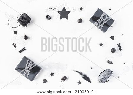Christmas composition. Christmas gifts pine cones black accessories on white background. Flat lay top view copy space