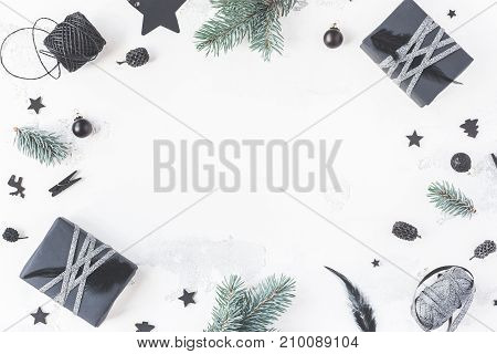 Christmas composition. Christmas gifts pine cones fir branches black decorations on white background. Flat lay top view copy space