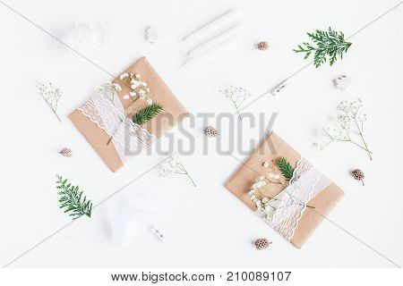 Christmas composition. Christmas gifts pine cones gypsophila flowers thuja branches on white background. Flat lay top view