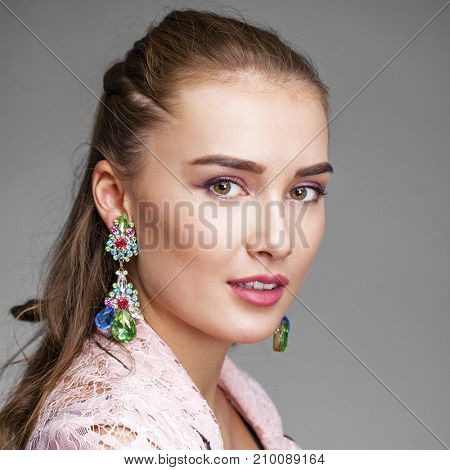 Portrait of beautiful young adult attractive  woman in pink elegance fashionable suit isolated on gray background