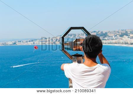 Nice France - 16.09.16: Boy looking through binoculars on a flying parachute in a beautiful sea in NiceFrance .