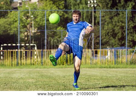 The soccer player is shooting the soccer ball on playing field.