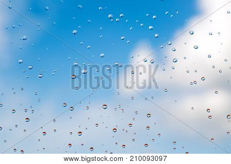 water drops rain on glass on background of blue sky