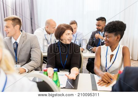 business and education concept - group of people talking at international conference