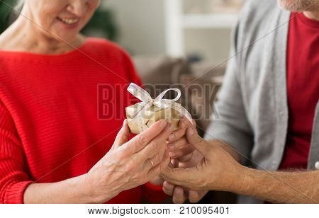 christmas, holidays and people concept - close up of happy smiling senior couple with gift box at home