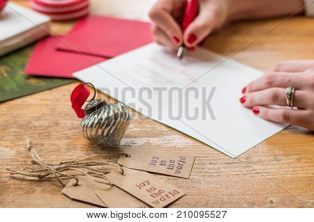 young woman writing christmas cards with red nails a red pen and holiday decorations on a wooden table