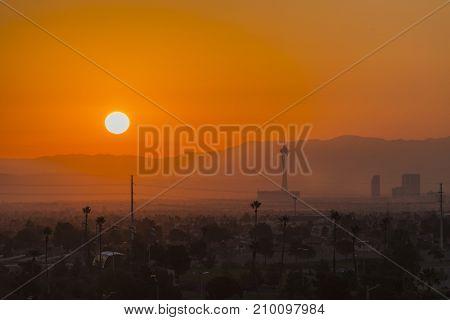 Las Vegas, Nevada, USA - October 13, 2017:  Hot Mojave desert sun rising behind the Stratosphere tower on the Las Vegas strip.
