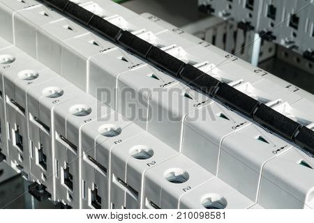 Modular circuit breakers installed in the electrical cabinet. Electrical cabinet assembly production. Installation of electrical equipment on the circuit board.