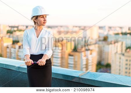 Pretty Young Forewoman In Helmet Stand On The Roof With Tablet In Hands, Look At Sunset