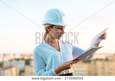 Pretty Young Forewoman In Helmet Stand On The Roof With Tablet In Hands