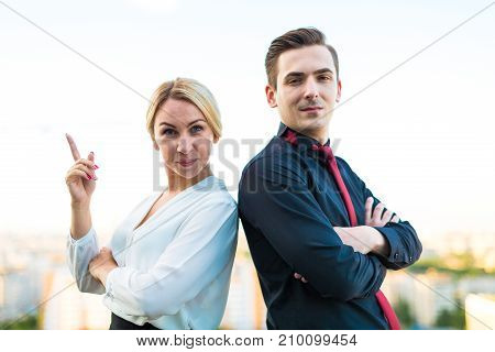 Couple Of Businessmen, Good Looking Brunette Man And Attractive Blonde Woman Stand On The Roof Back