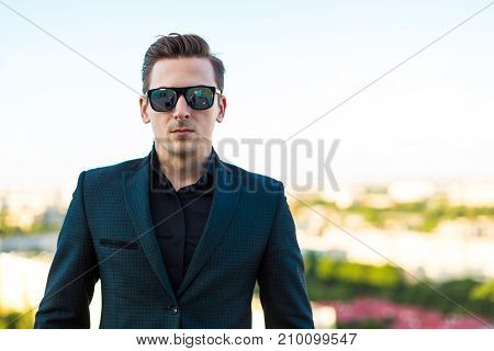 Young Serious Busunessman In Dark Suit, Sunglasses, Watch And Black Shirt Stand On The Roof