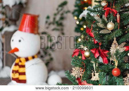 Christmas ball and garland on the fir tree. snowman on the background