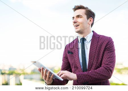 Serious Businessman In Red Suit And Shirt With Tie Stand On The Roof With Empty Tablet