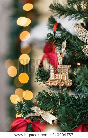 Christmas toy train and garland on the fir tree. vertical photo
