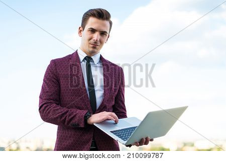 Serious Businessman In Red Suit And Shirt With Tie Stand On The Roof With Laptop