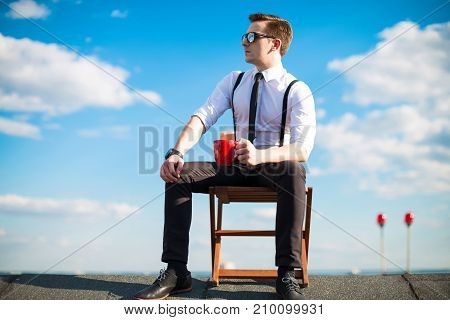 Attractive Serious Busunessman In White Shirt, Tie, Braces And Sunglasses Resting On The Roof, Hold