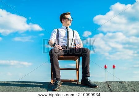 Attractive Serious Busunessman In White Shirt, Tie, Braces And Sunglasses Resting On The Roof