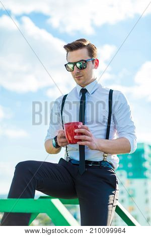 Attractive Young Busunessman In White Shirt, Tie, Braces And Sunglasses With Red Cup