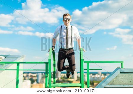Young Busunessman In White Shirt, Tie, Braces And Sunglasses Stand On The Roof Ladder