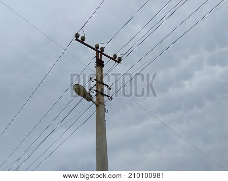 Old holder of the electrical installation with lighting against the sky