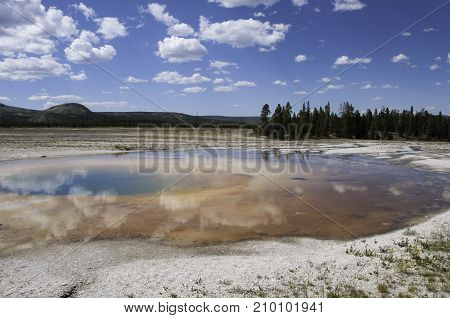 reflection of clouds in a sulfur pool at Yellowstone National Park