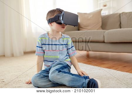 technology, augmented reality, entertainment and people concept - little boy with virtual headset or 3d glasses playing at home