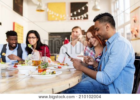 leisure, technology and people concept - group of happy international friends with smartphones at restaurant table
