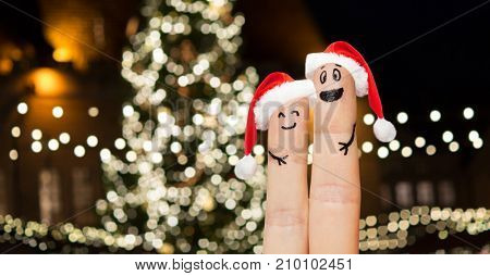 holidays and body parts concept - close up of two fingers in santa hats with smiley faces over christmas tree lights background
