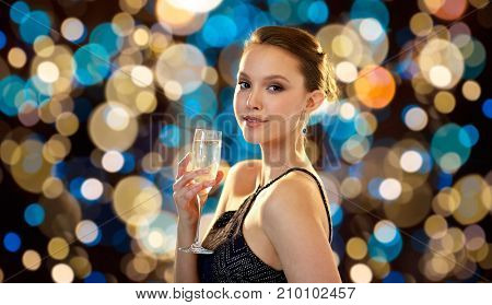 people and luxury concept - beautiful young asian smiling woman drinking non alcoholic champagne at party over holidays lights background