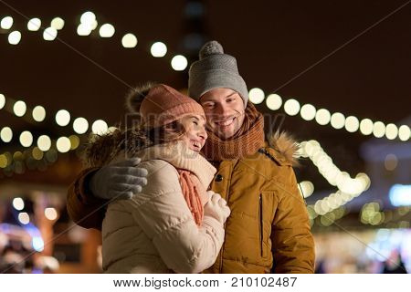 winter holidays and people concept - happy young couple dating and hugging in christmas evening outdoors