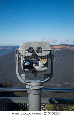 This image was taken in the Blue Mountains of New South Wales, Australia. It features an optical telescope in the foreground and a section of the Blue Mountains in the background. This picture was taken midday in the Australian Winter in July.