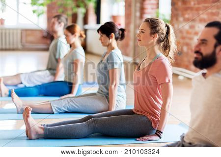 fitness, sport and healthy lifestyle concept - group of people doing yoga seated staff pose on mats at studio