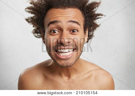 Happy Mixed Race Man Smiles Happily As Recieves Pleasant Comments From Clients, Demonstrates White P
