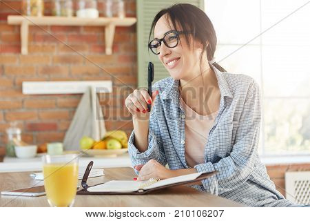 Happy Woman With Appealing Appearance, Going To Organize Party, Makes List Of Invited Friends, Sits