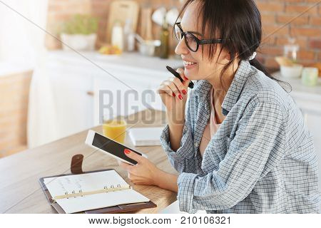 Good Looking Brunette Female Being At Home, Uses Modern Tablet For Making Contacts With Friends Or R